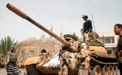 Pro-government fighters gather next to a tank they use in the fighting against Houthi fighters in the southwestern city of Taiz, Yemen, on March 22, 2017.
