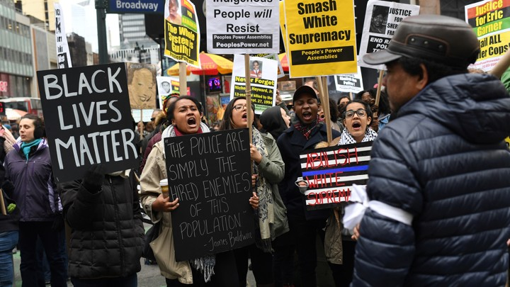 "Black Lives Matter activists hold signs reading, ""Black lives matter,"" ""smash white supremacy,"" and ""brown and indigenous people will resist."""