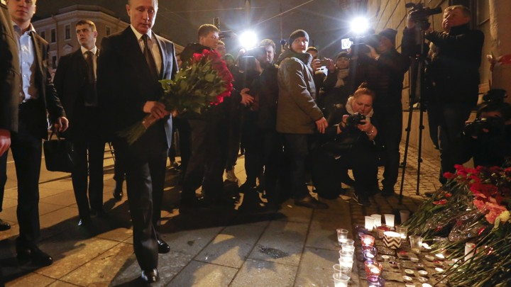Russian president Vladimir Putin puts flowers down outside Tekhnologicheskiy Institut metro station in St. Petersburg, Russia.