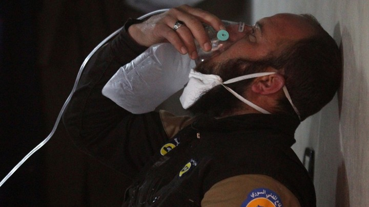 A civil defense member breathes through an oxygen mask, after what rescue workers described as a suspected gas attack in the town of Khan Sheikhoun.