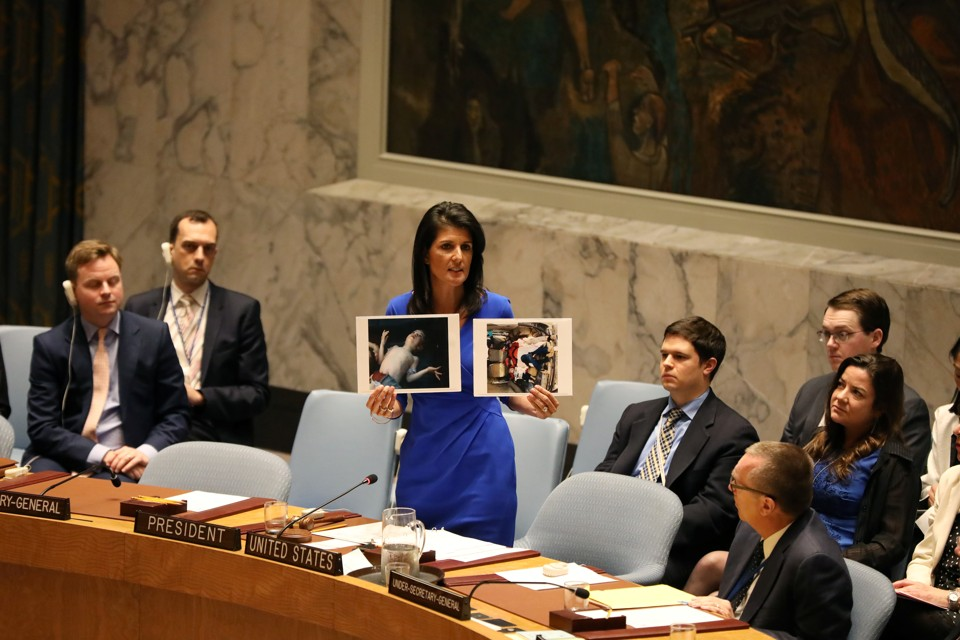U.S. Ambassador to the United Nations Nikki Haley holds photographs of victims during a meeting at the United Nations Security Council on Syria at the United Nations headquarters on April 5, 2017.