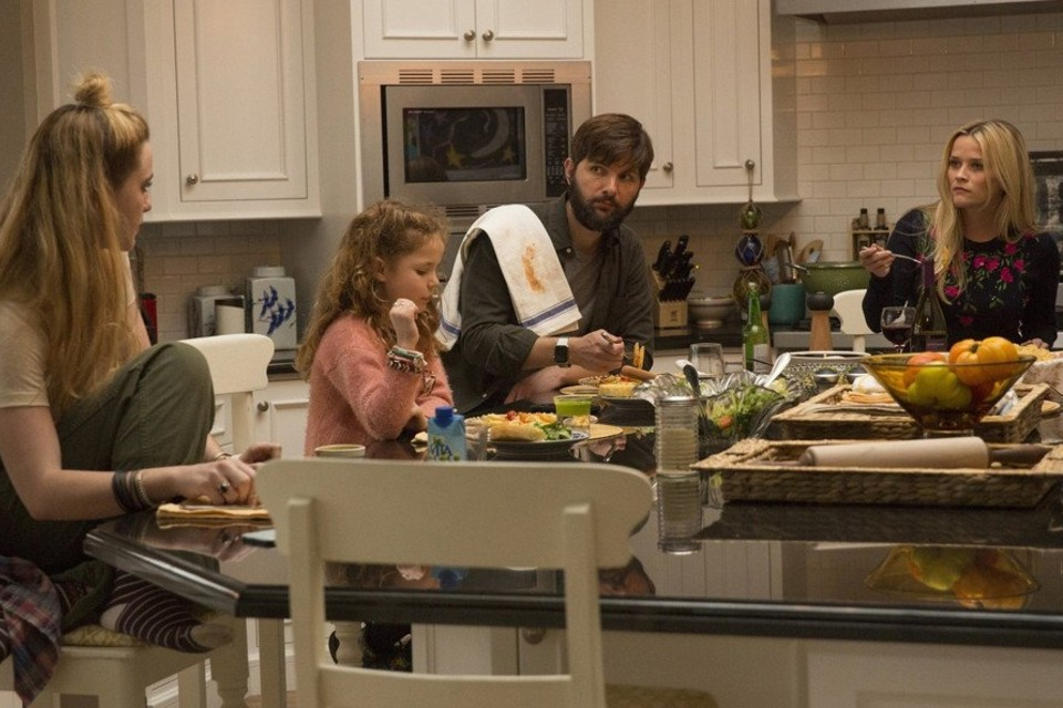 "A screenshot of ""Big Little Lies"" featuring the actress Reese Witherspoon and her characters' husband and children."