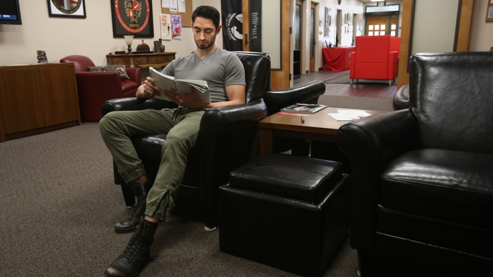 A man sits in a leather chair reading a textbook.