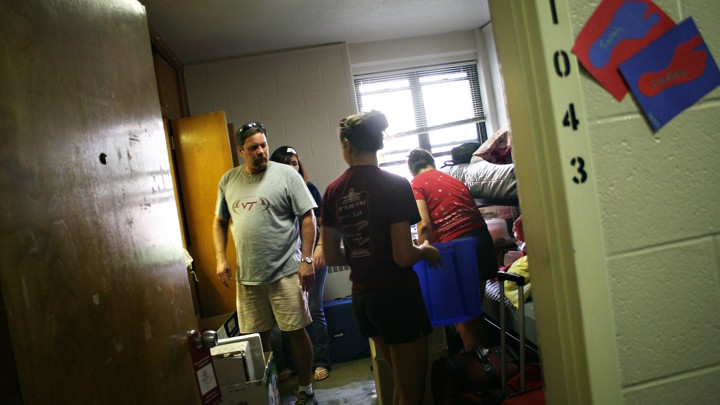 A family unpacks a student's luggage and furniture in a dorm room.