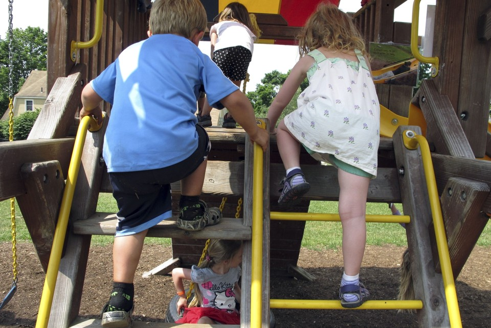 A boy and girl climb up a swing set.