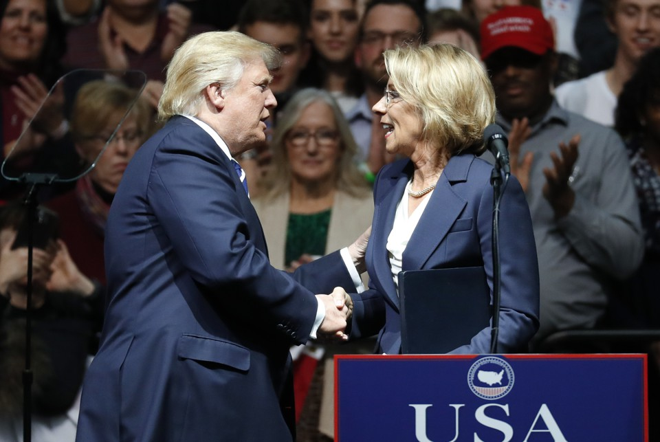 Betsy DeVos and Donald Trump shake hands