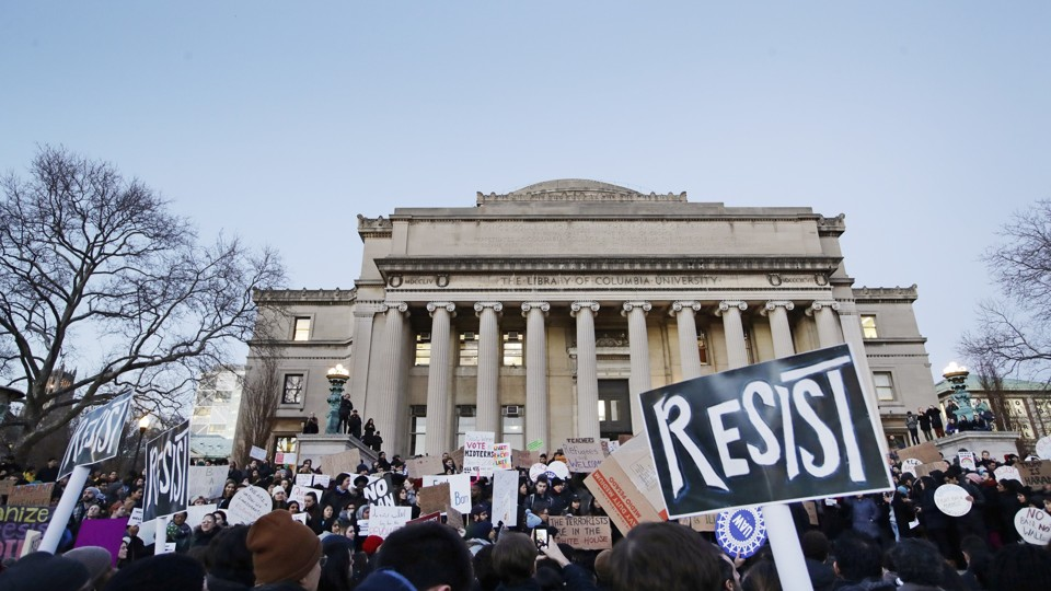 """A group of students holds signs that read """"resist"""" outside the Columbia University Library."""