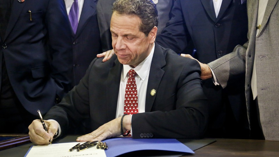 Andrew Cuomo signs a bill. There are six other pens he does not appear to be using but that stand at the ready should the ink run dry.