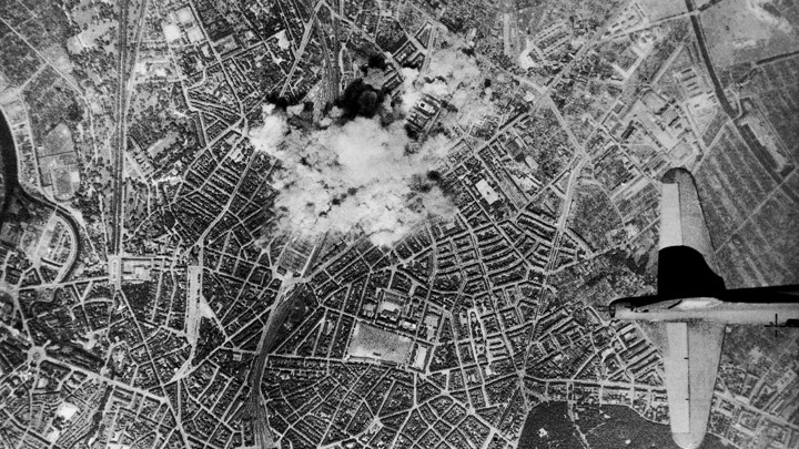 Bombs from U.S. Flying Fortresses explode on the Vahrenwalder-Strasse, in Hannover, Germany, where rubber tires for the German war machine are produced