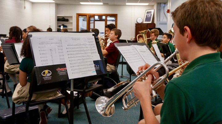 Students play band instruments including trumpets, tubas, and French horns.