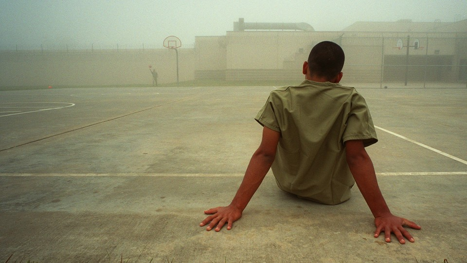 A boy sits in an outdoor recreation area at the Liberty County Jail in Texas.
