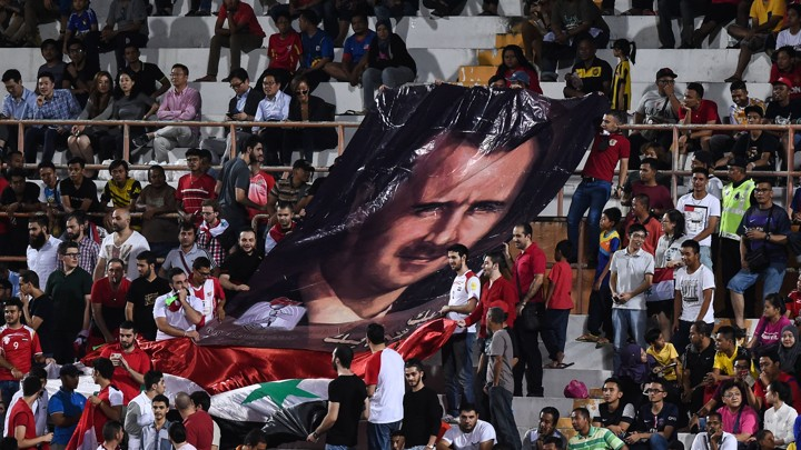 Syrian football supporters display a portrait of Syrian President Bashar al-Assad during the 2018 World Cup qualifying football match between South Korea and Syria.