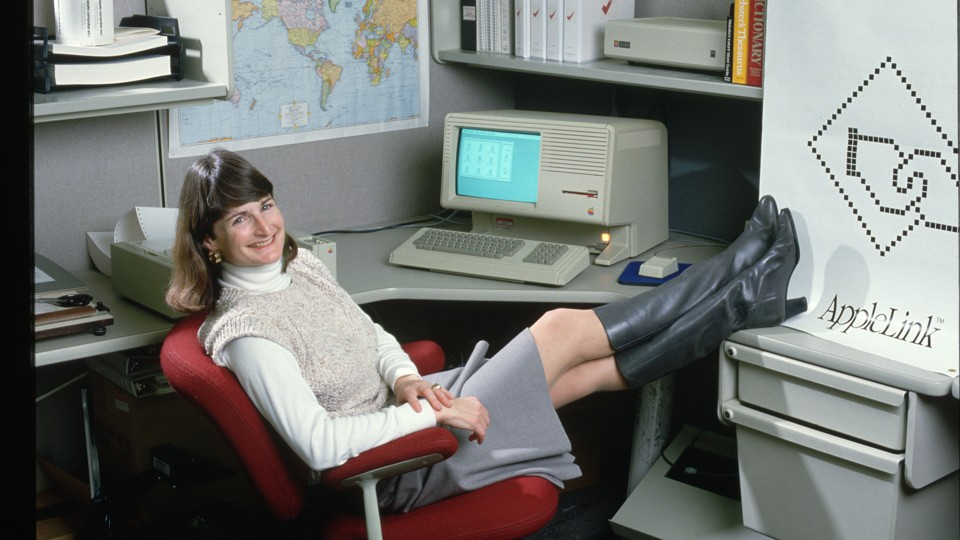 An Apple employee poses with a personal computer in 1986.