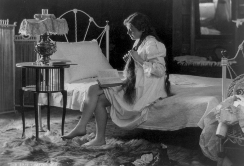 A young woman reads at the corner of her bed as she braids her hair.