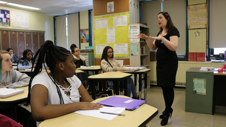 A woman stands at the front of a classroom as her students listen.