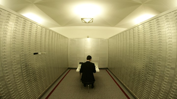 An employee sits amongst safe boxes in a safe room at a Swiss bank
