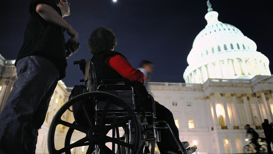A woman in a wheelchair sits in front of the U.S. Capitol in Washington, D.C.