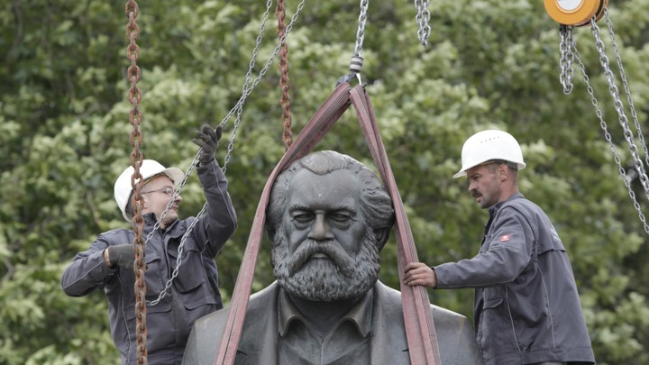 Workers in Berlin attach chains to lift a statue of Karl Marx.