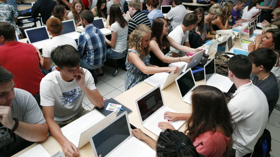 Students sit with Mac laptop computers