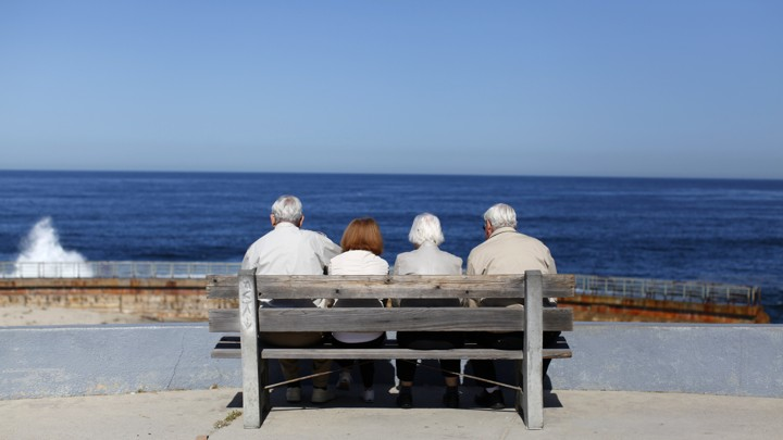 Four elderly people sit on a bench
