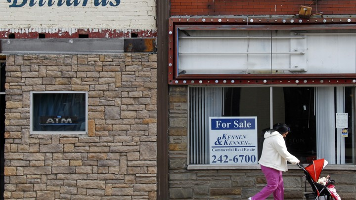 A woman pushes a baby carriage in the Rust Belt town of Wheeling, West Virginia.