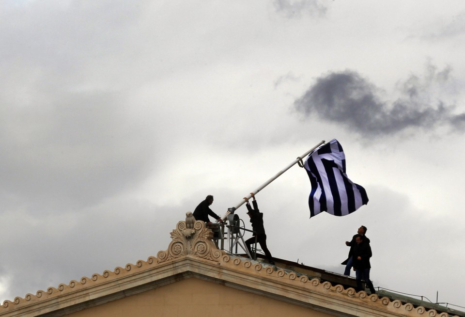 Greek parliament employees raise a mast after they replaced torn-off Greek flag with a new one atop the parliament in Athens Syntagma (Constitution) square on April 18, 2012.