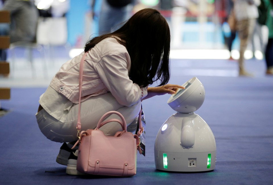 A woman interacts with a small robot.