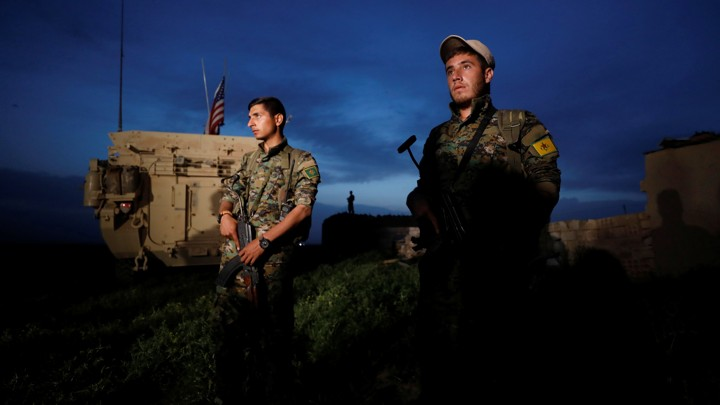 Kurdish fighters from the People's Protection Units (YPG) stand near a U.S military vehicle in the town of Darbasiya next to the Turkish border, Syria, on April 28, 2017.