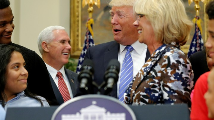 Vice President Mike Pence, President Donald Trump, and Education Secretary Betsy DeVos are seen laughing at a school-choice event in Washington, D.C.