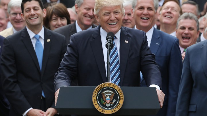 President Donald Trump celebrating in the Rose Garden surrounded by Republican congresspeople