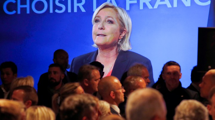 Marine Le Pen, French National Front (FN) political party candidate for French 2017 presidential election, is seen on a screen while conceding defeat.