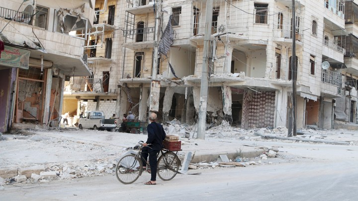 A man on a bicycle inspects a damaged building in eastern Aleppo in 2015.