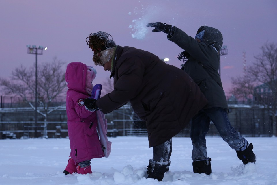 An adult comforts one child while another throws a snowball behind them.