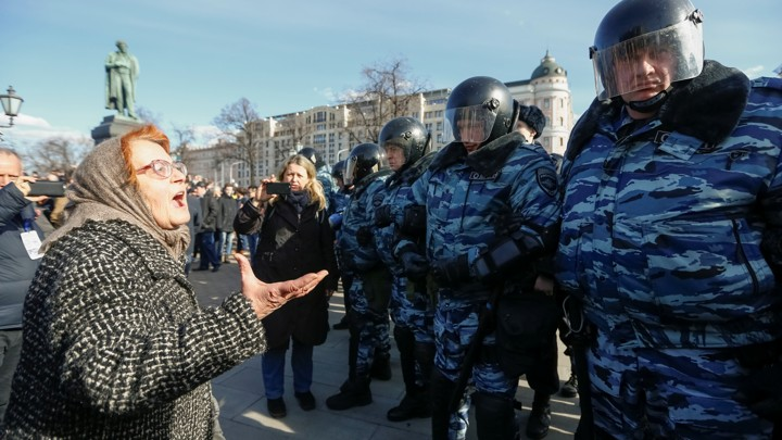 A woman argues with law enforcement officers as they block a rally in Moscow.