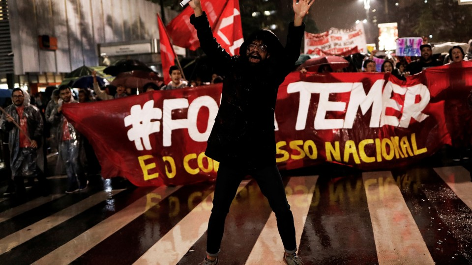 """Demonstrators take part in a protest against Brazil's President Michel Temer in Sao Paulo, Brazil, on May 18, 2017. The banner reads """"Out Temer."""""""