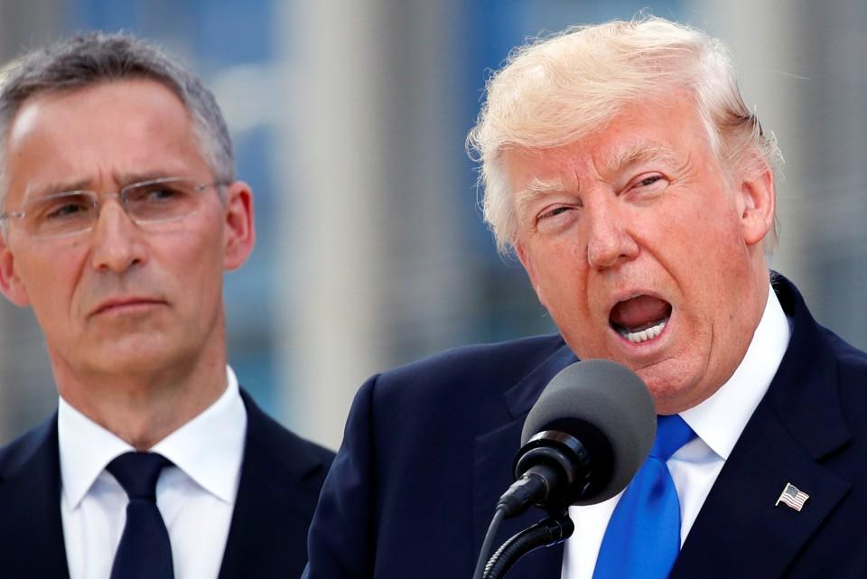 President Donald Trump speaks beside NATO Secretary General Jens Stoltenberg at the start of the NATO summit.