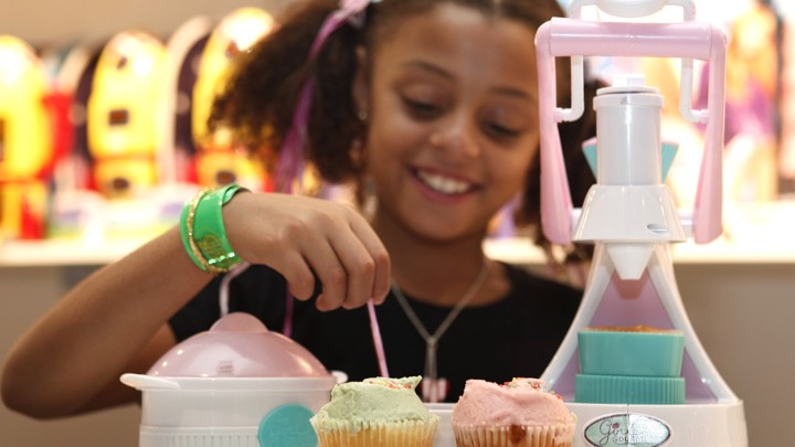A girl poses with a cupcake-maker toy at the Dream Toys exhibition in London, in 2008.