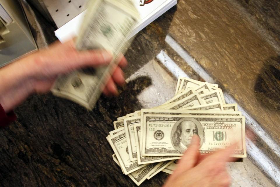 A bank teller counts money.