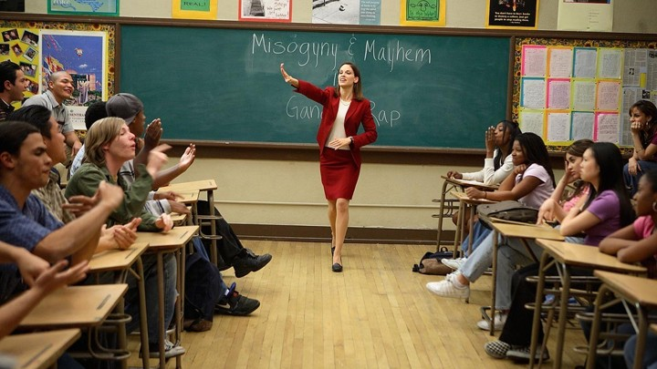 "An actress stands in a red skirt and blazer at the front of a classroom. ""Misogyny and Mayhem in Gangster Rap"" is written on the chalkboard behind her."