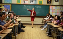 """An actress stands in a red skirt and blazer at the front of a classroom. """"Misogyny and Mayhem in Gangster Rap"""" is written on the chalkboard behind her."""
