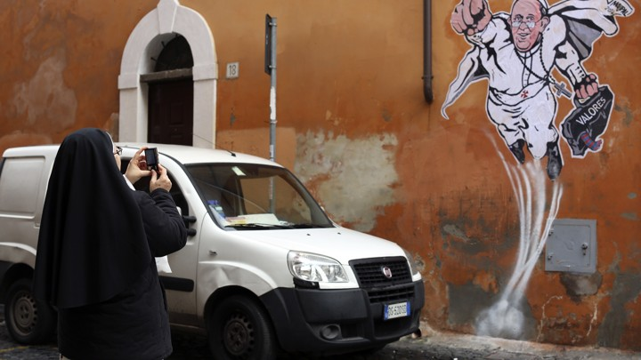 A nun takes a picture of a drawing of Pope Francis depicting him as a superhero on a wall near the Vatican.