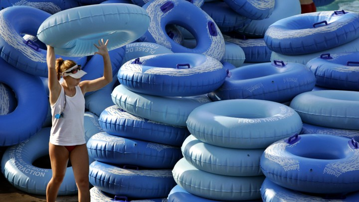 a waterpark employee stacks inner tubes