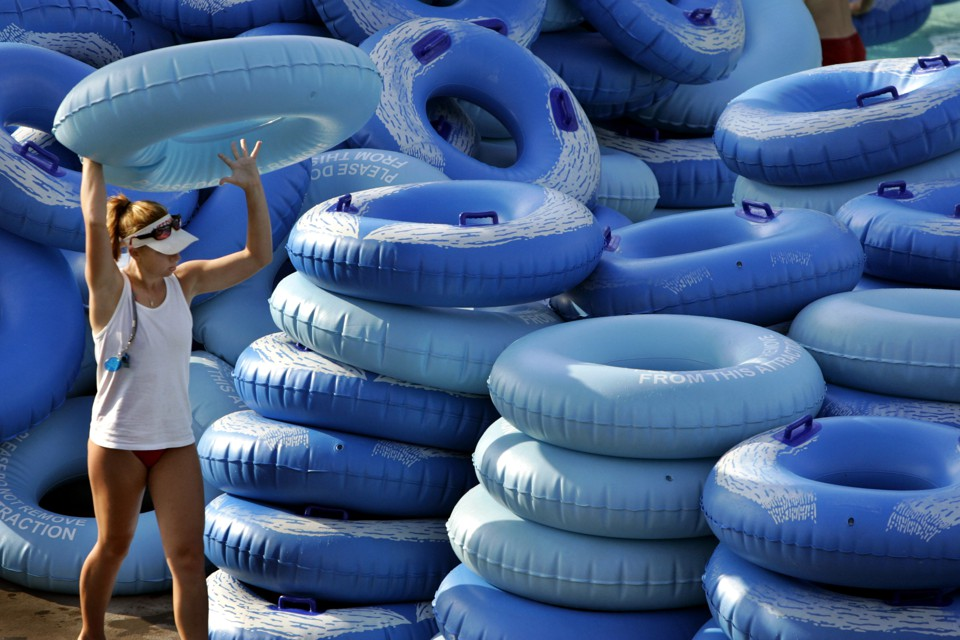 A waterpark employee stacks inner tubes.