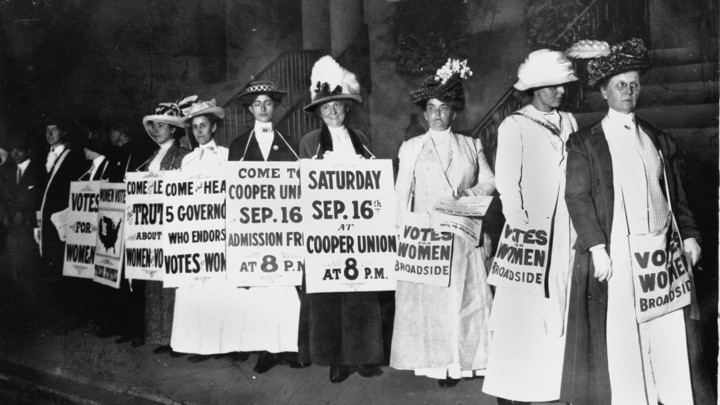 A black and white photo of women in dresses and feathered hats. They hold signs advertising an upcoming rally for women's right to vote.