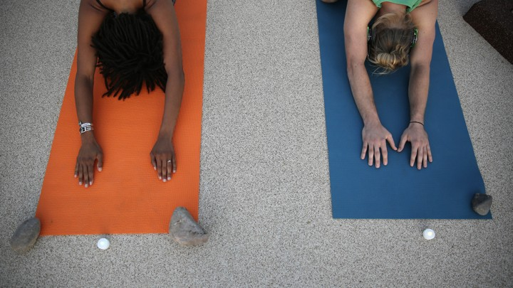 Two people practice yoga