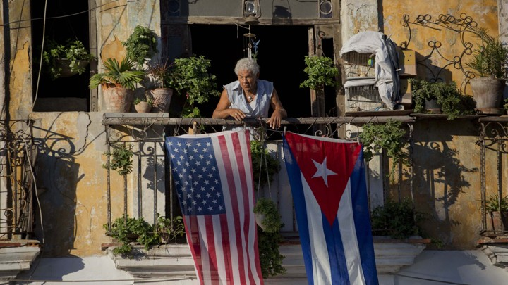 Javier Yanez stands on his balcony decorated with U.S. and Cuban flags in Old Havana, Cuba.
