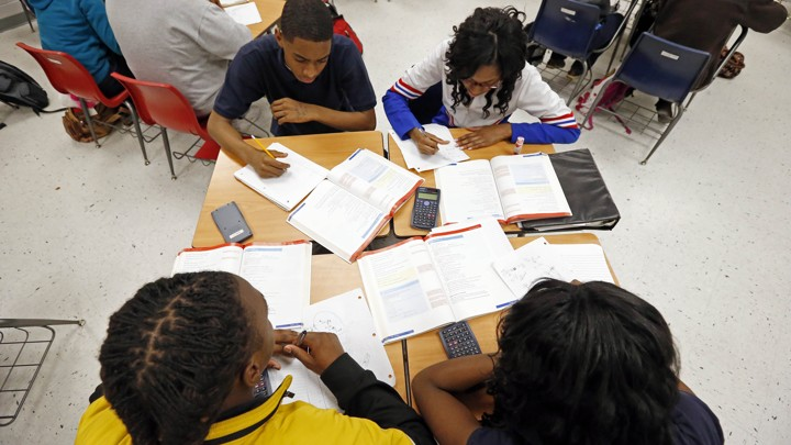 An overhead shot of students with calculators and textbooks
