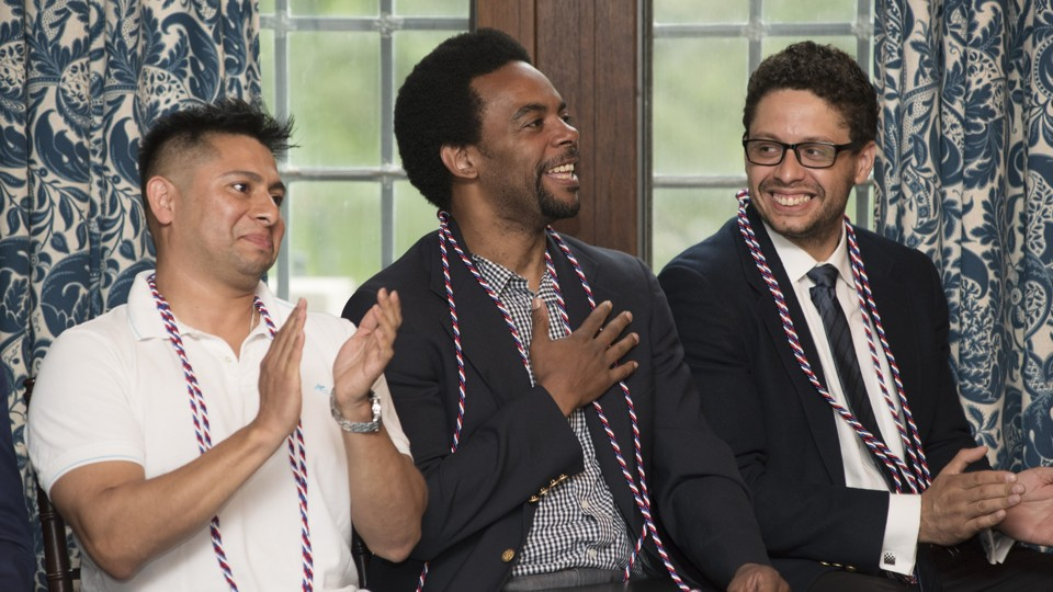 Three men sit with red and white graduation chords. One has his hand over his heart