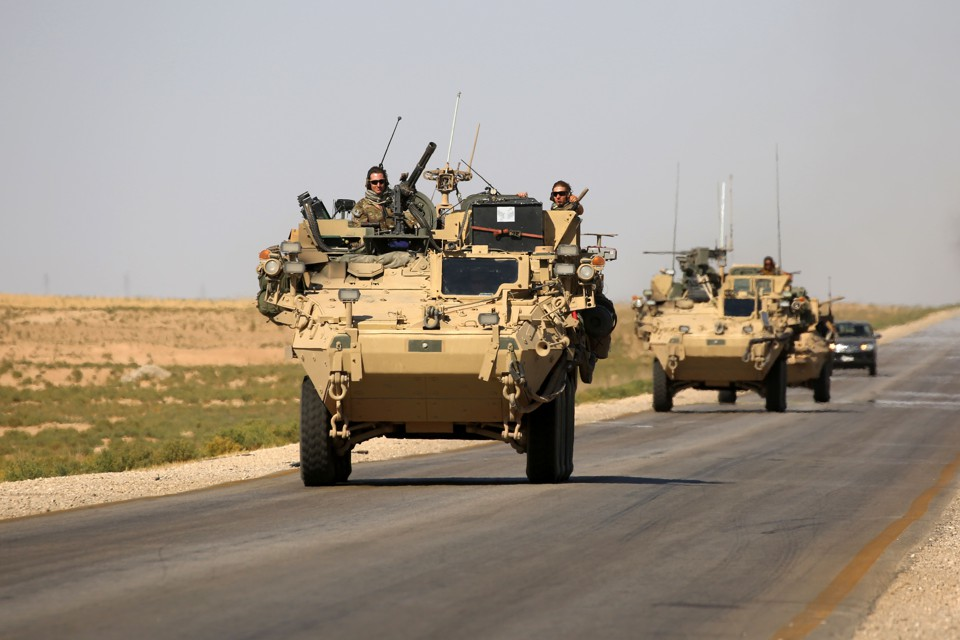 U.S. troops sit atop an armored vehicle on a road near the northern Syrian village of Ain Issa on June 3, 2017.