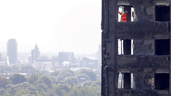 Members of the emergency services work inside the charred remains of the Grenfell Tower block on June 17, 2017.